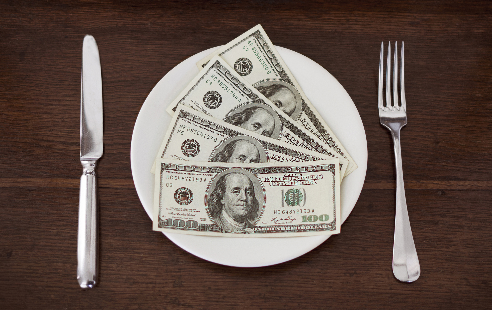 Table setting with money on the plate